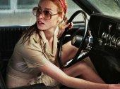 La dame dans lauto avec des lunettes et un fusil